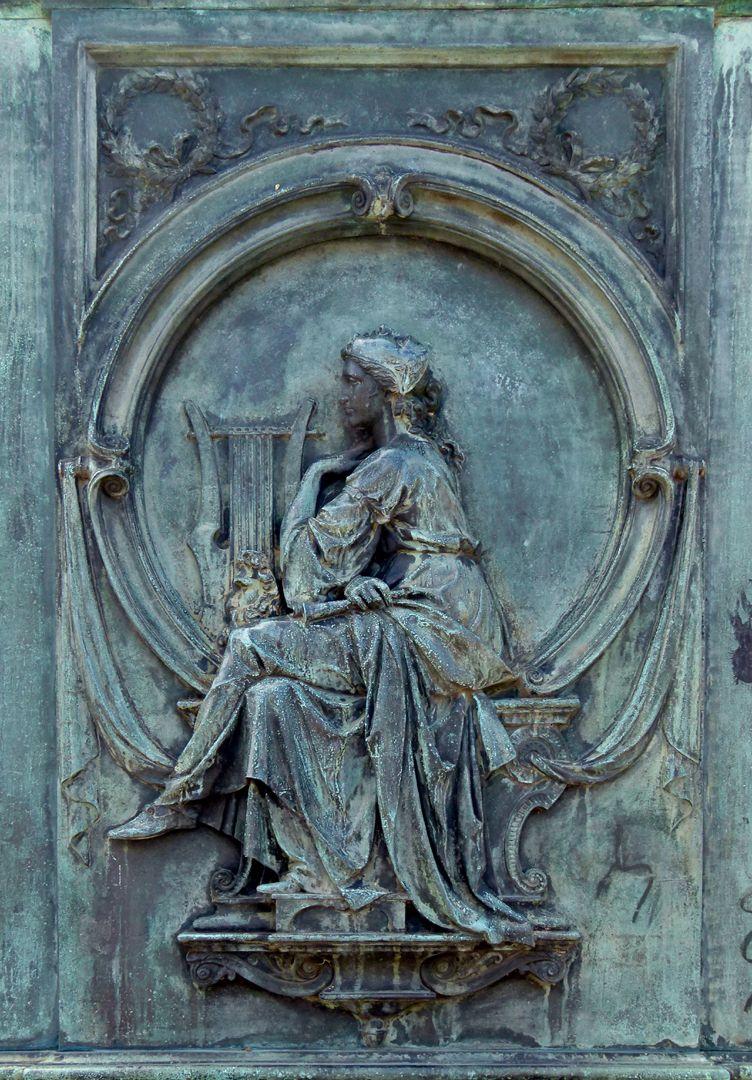 Beethoven-Denkmal (Bonn) Sockelrelief, links unterhalb von Beethoven; Frauengestalt mit Lyra-Harfe, einer griechischen Maske auf ihrem Schoß und einer Maske auf dem Kopf