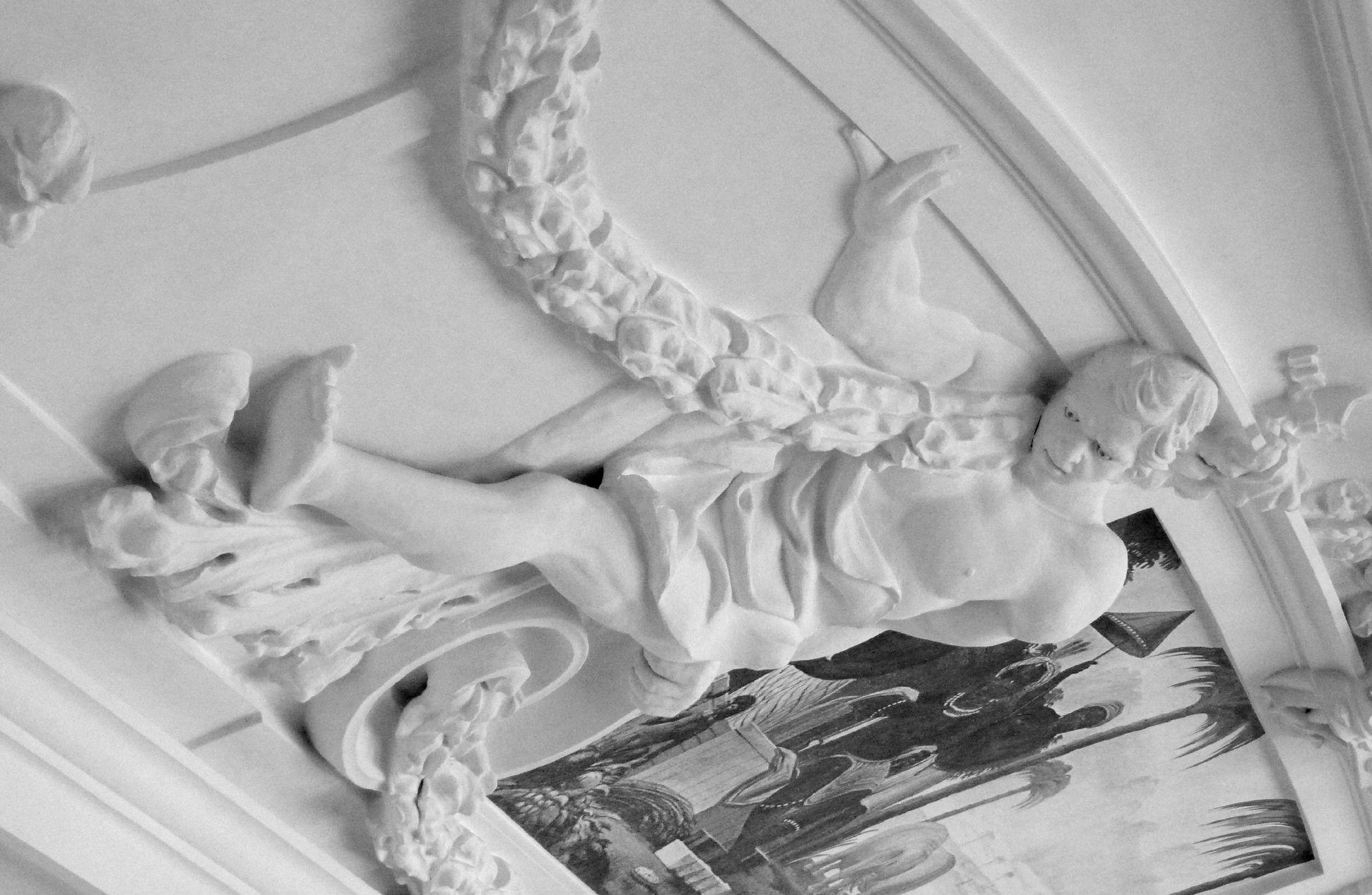 Stuckdecke aus dem Gartensaal des ehemaligen Merkelschen Anwesen Auf einer Volute sitzender Mann mit Girlande in südöstlicher Zimmerdecke, Schrägansicht