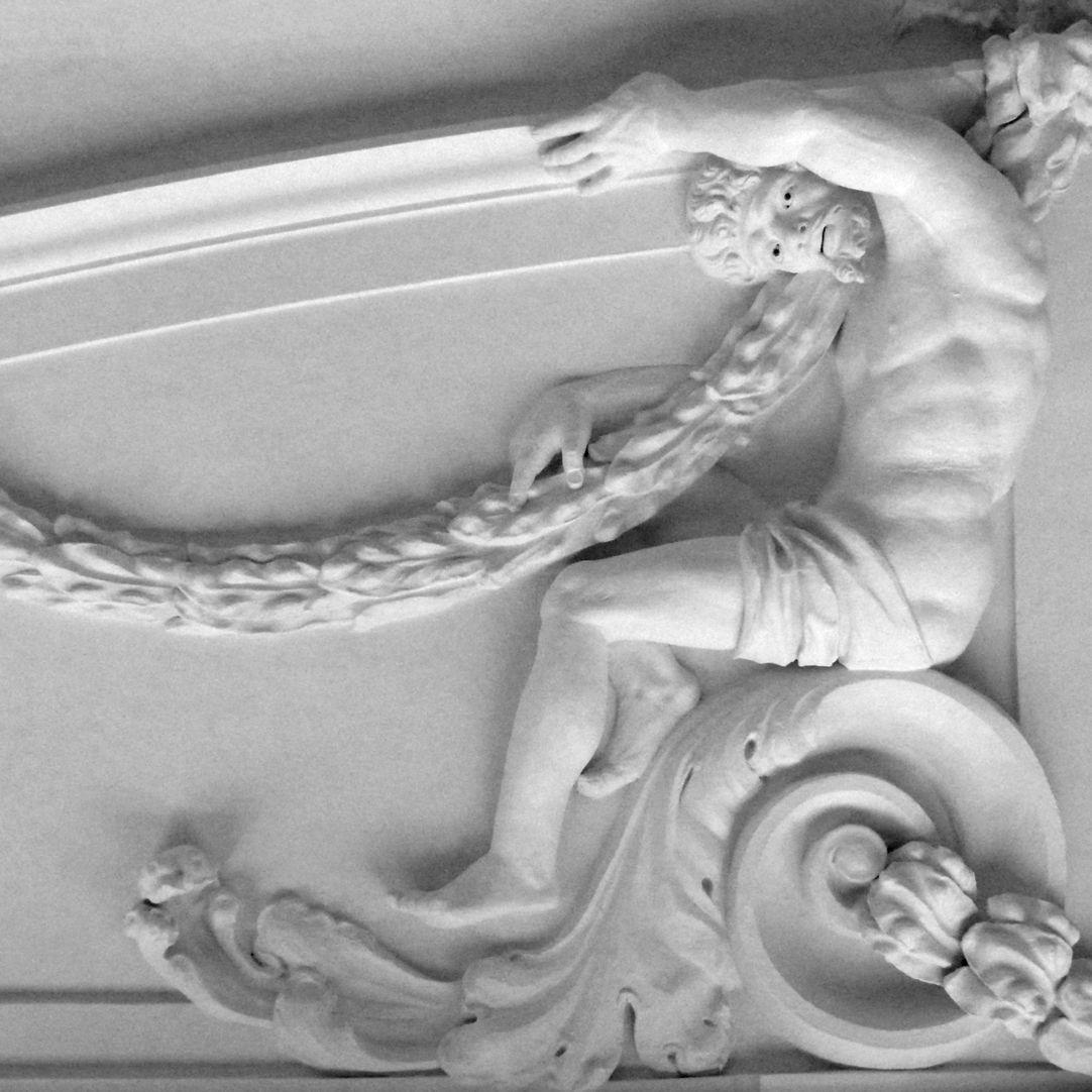 Stuckdecke aus dem Gartensaal des ehemaligen Merkelschen Anwesen Auf einer Volute sitzender Mann mit Girlande in nordwestlicher Zimmerdecke