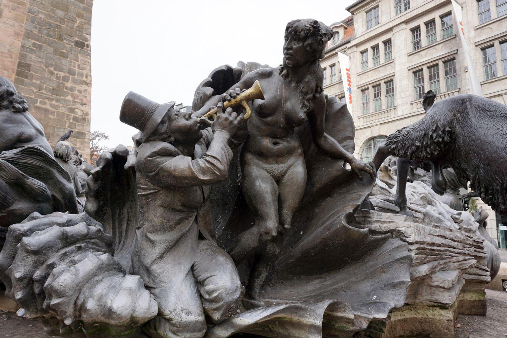 """Ehekarussell / Hans-Sachs-Brunnen """"Venusmuschel"""" / """"Er besingt die nackte Schönheit mit seinem Instrument, die Muschel wird zur Jahrmarktbude"""" (J.W.)"""