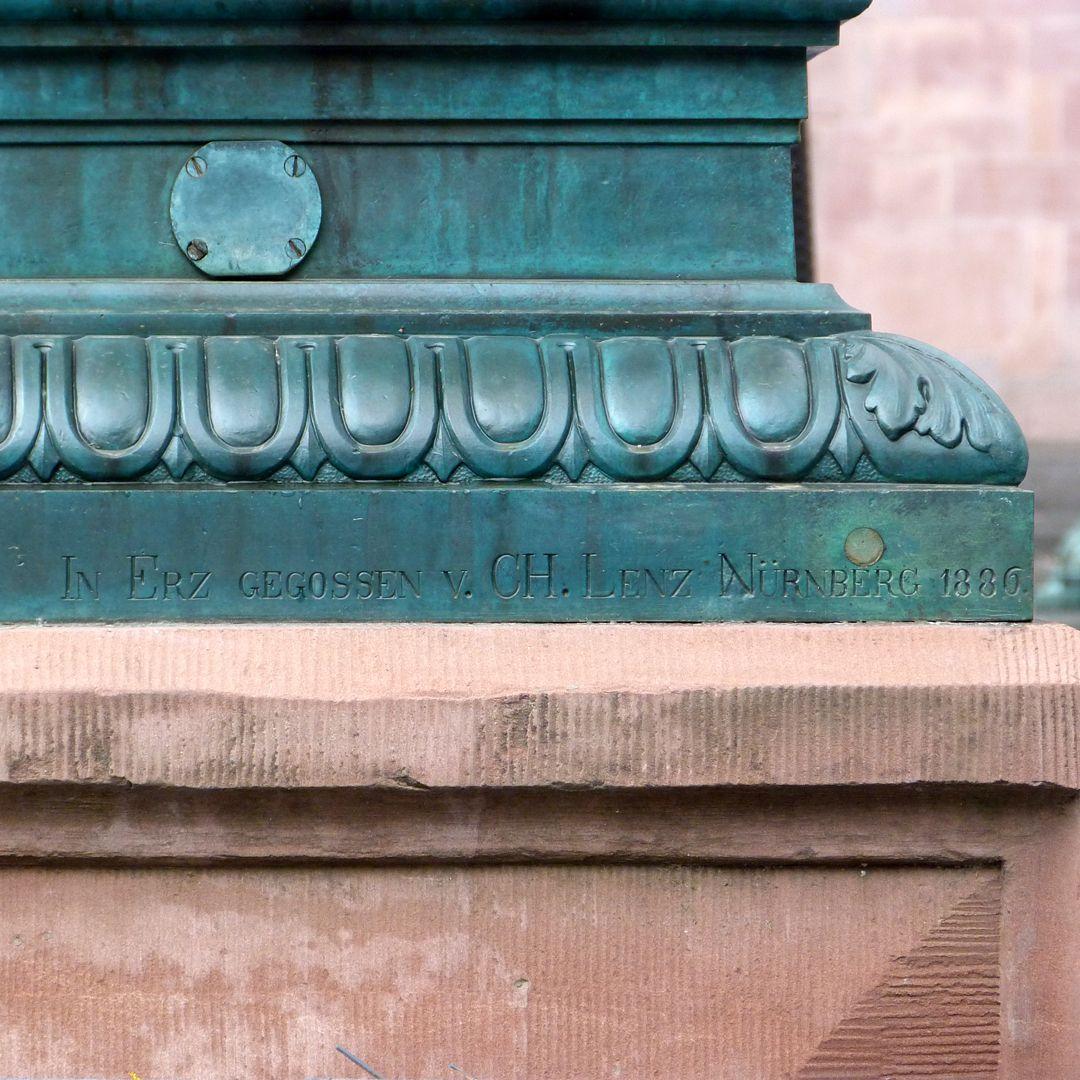 Gerechtigkeitsbrunnen (Frankfurt a.M.) Inschrift: In Erz gegossen von Ch. Lenz. Nürnberg 1886 (Ostseite des Brunnenstocks)