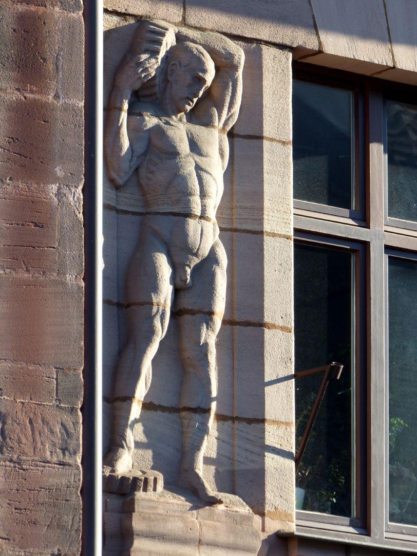 Geschäfts- und Bürohaus, Hefnersplatz 7 Arbeiter mit zwei Zahnrädern, Relief am vierten Obergeschoss