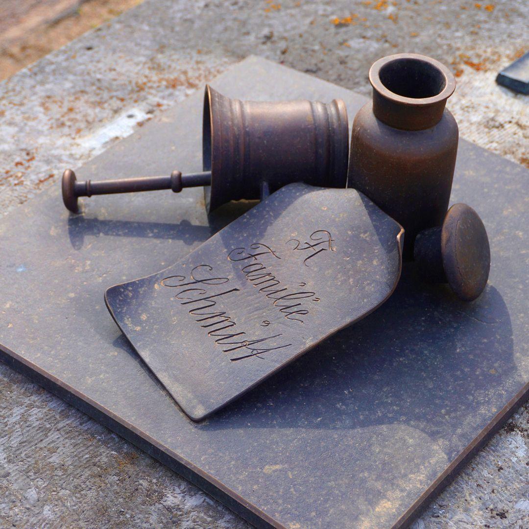 Johannisfriedhof Grabstätte II H 30 Ein liegender Mörser mit Stößel, ein Zettel mit Familennamen und eine geöffnete Apothekerflasche mit Glasstopfen