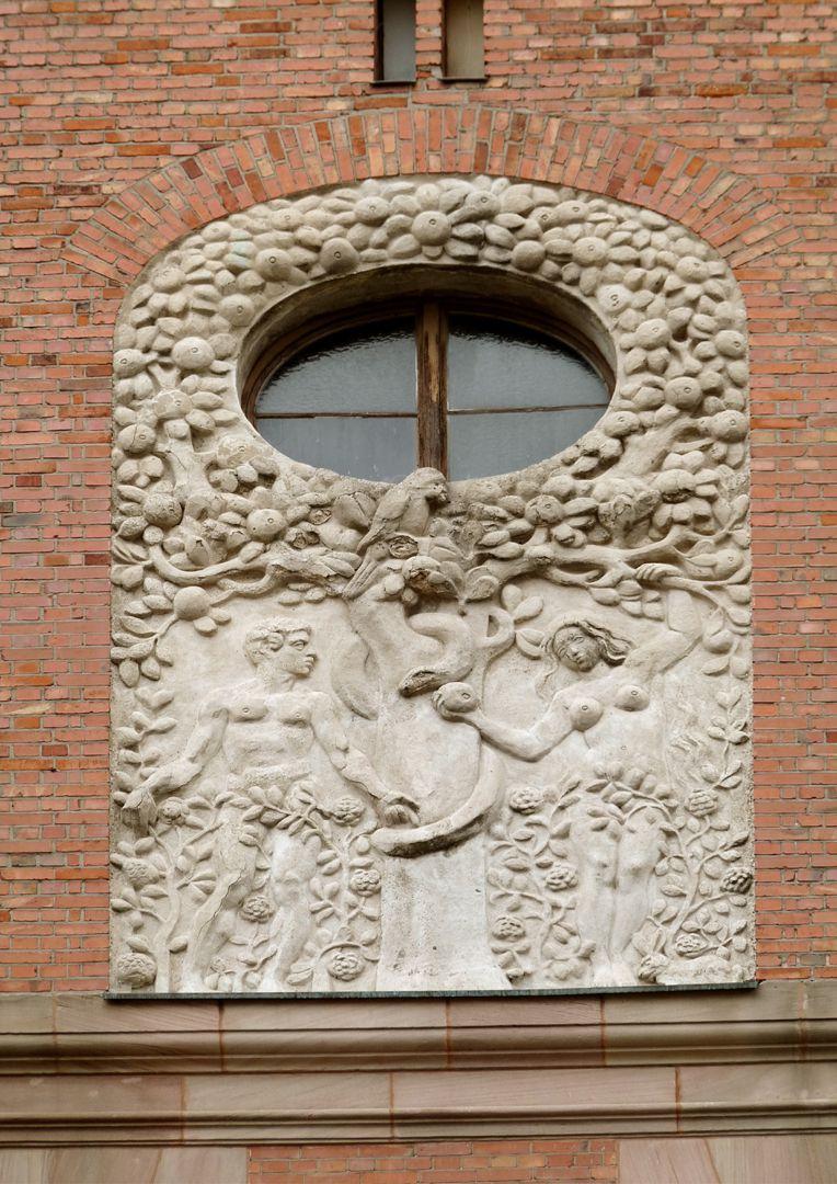 Dr. Theo-Schöller-Schule Relief der Zwillingsgiebel: Adam und Eva (nach der Frucht der Erkenntnis greifend)