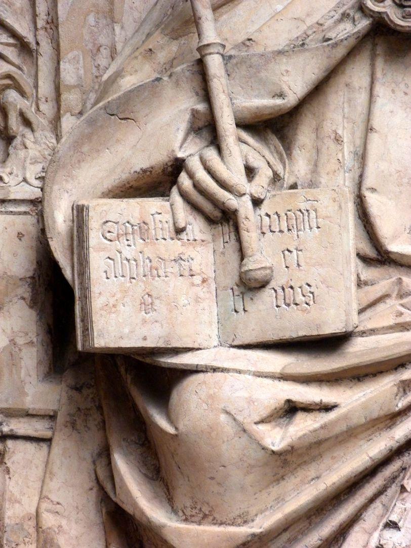 """Epitaph des Kunz Horn Aufgeschlagenes Buch mit dem lateinischen Spruch für """"Ich bin Alpha und Omega, Anfang und Ende""""."""