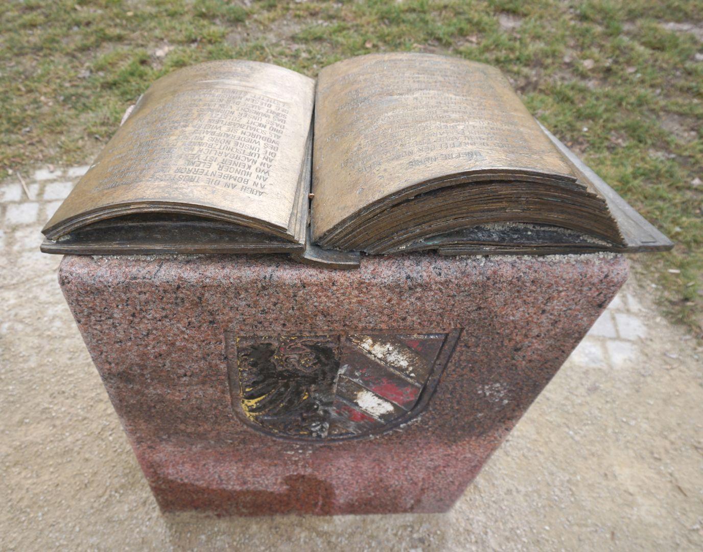 Norisbrunnen Aus der Bindung gehendes bronzenes Buch mit Stifterwidmung auf einem Steinpult mit Stadtwappen