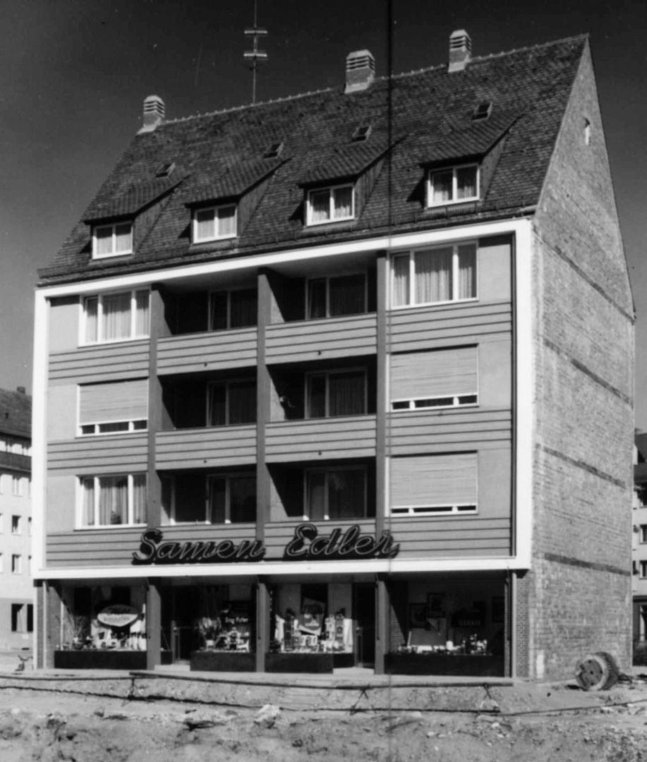 Wohn- und Geschäftshäuser viergeschossiges Traufenhaus, Achsensymmetrisch mit mittleren zurückspringenden Balkonen, gerahmt von einem leicht vorkragenden Rechteck