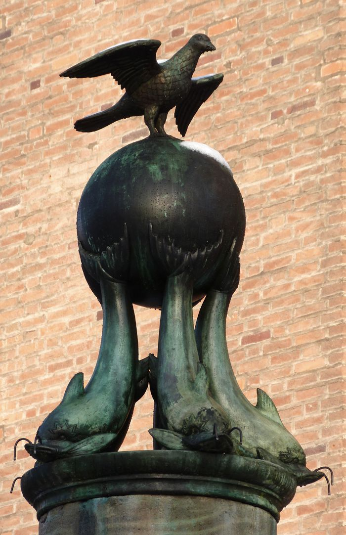 Symbolbrunnen Brunnenfigur von Südost: Ein Vogel sitzt auf einer von Delphinen getragenen Kugel