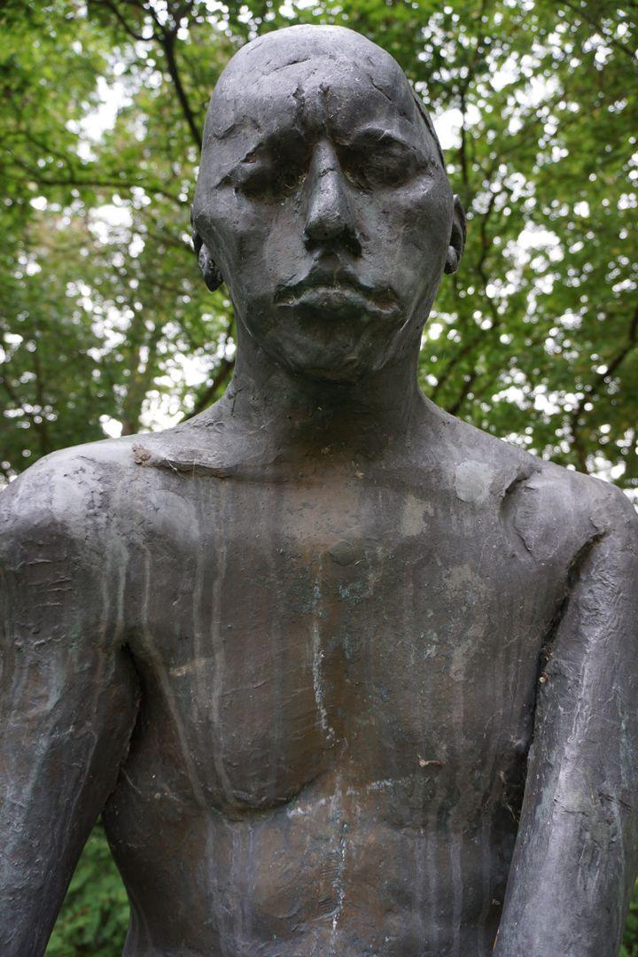 Sitzende Bronzefigur Oberkörper, Untersicht von vorne